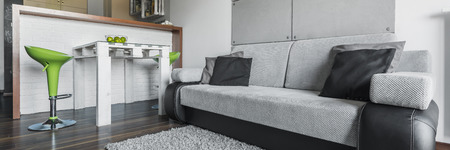 dining table and chairs: Panoramic view of big comfortable grey sofa and dining table with chairs in modern apartment