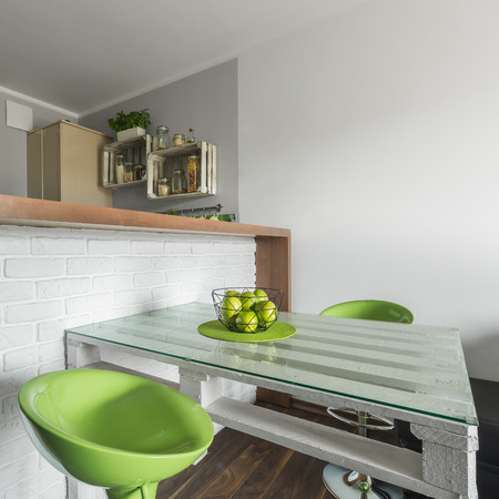 dining table and chairs: Modern apartment with decorative brick wall at dining area with table, and two green chairs