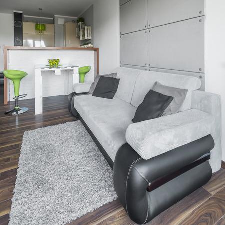 #62106439   Große Graue Couch Im Stilvollen Wohnzimmer Design In Grau Mit  Modernen Grünen Dekorationen Und Küchenbereich Hinter Mauer