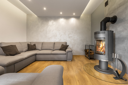 extra large: Grey living room with a fireplace, extra large sofa, floor panels and decorative wall plaster