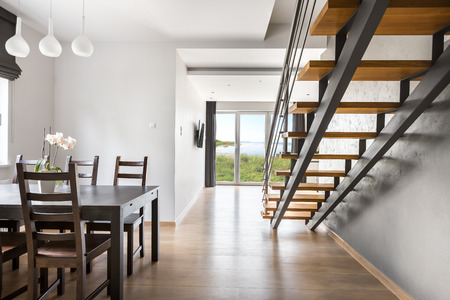 Light villa interior with dark dining set, staircase, wooden floor panels, balcony doors in the background Stock Photo