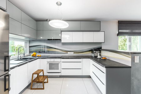 Light and spacious kitchen with white furniture, high gloss tiling and window