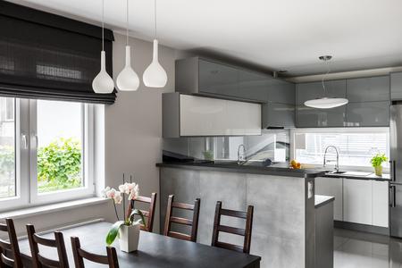 シンプルなダイニング セット、装飾的なペンダン トランプ、巻上げ式ブラインド、背景に光のオープン キッチン