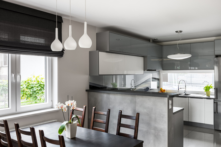 Simple dining set, decorative pendant lamp and roller blinds, light open kitchen in the background Foto de archivo