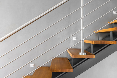 chromed: Villa interior with staircase with chromed railing and decorative grey wall finish