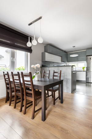 lamp window: Simple dining room with solid table, chairs, pendant lamp, window roller blind and floor panels, open kitchen in the background Stock Photo