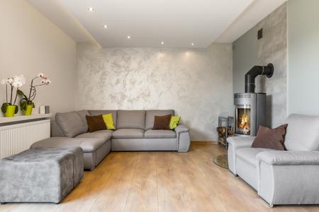 #63351130   Geräumiges Wohnzimmer Mit Extra Großen Sofa, Kamin Im Industriellen  Stil, Holzbodenplatten Und Dekorative Wandfinish