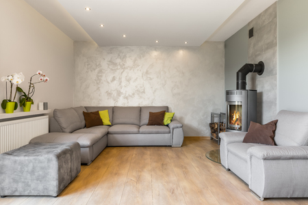 Spacious living room with extra large sofa, fireplace in industrial style, wood floor panels and decorative wall finish