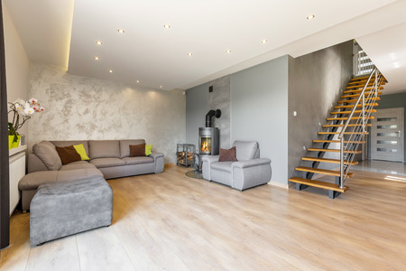 extra large: Modern villa interior with extra large sofa, fireplace in industrial style, wood floor panels, decorative wall finish and wooden stairs