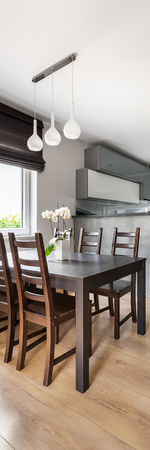lamp window: Vertical panorama of simple dining space with solid table, chairs, pendant lamp, window roller blind and floor panels, open kitchen in the background