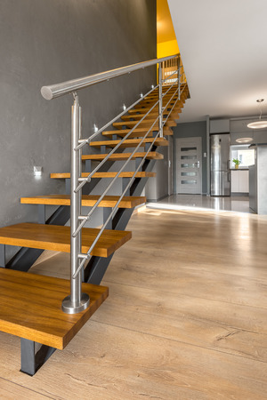 Villa interior with modern wooden stairs, floor panels, in the background white doors and open kitchen
