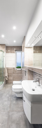 bidet: Vertical panorama of spacious beige bathroom with white basin, mirror, toilet, bidet and shower in background