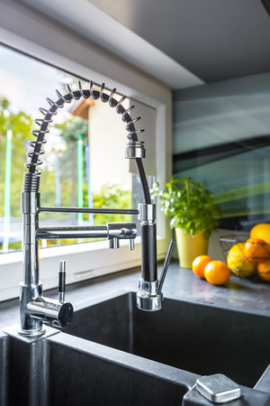 double sink: Close up of a double basin kitchen sink, solid worktop and window