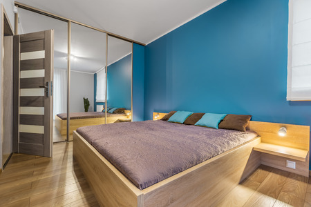 mirrored: Spacious new design bedroom with large bed, mirrored wardrobe and wooden floor panels