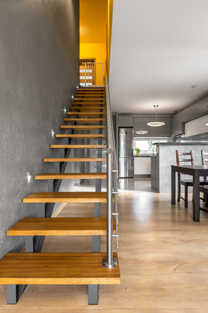Grey villa interior with wooden stairs and simple dining area open to kitchen