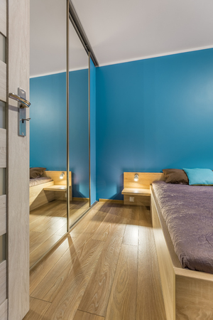 mirrored: Blue bedroom with large bed, mirrored wardrobe and floor panels