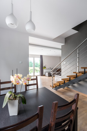 dining table and chairs: Image of dining table and chairs, in the background stairs and open living room Stock Photo