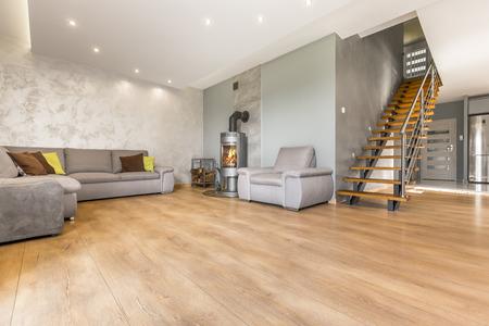 초대형 소파, 벽난로, 베네치아 석고 및 나무 계단을 갖춘 넓은 오픈형 거실 스톡 콘텐츠