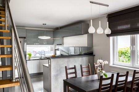 Light open space apartment with dining area, kitchen and wooden staircase