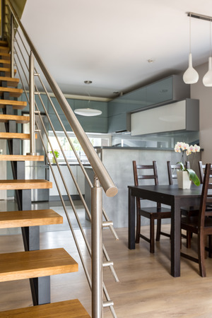 chromed: Image of wooden staircase with chromed railing, in the background dining set and open kitchen