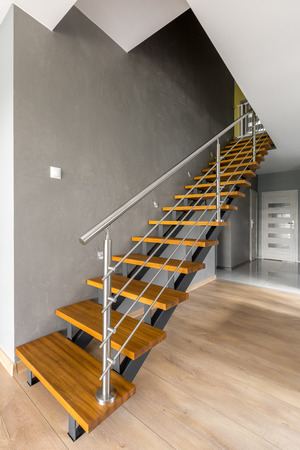chromed: Image of design wooden stairs with chromed railing, white doors in the background