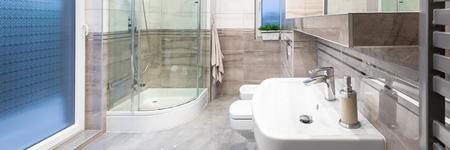 #63530738   Panorama Der Geräumige Und Moderne Badezimmer In Weiß Und Beige  Mit Fenster, Eine Begehbare Dusche Und Klassischen Becken