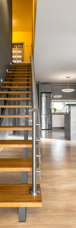 chromed: Vertical panorama of simple and modern wooden stairs with chromed railing Stock Photo