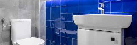 bathroom tiles: Panorama of bathroom with grey matt tiles and blue glossy tiles, white toilet and sink