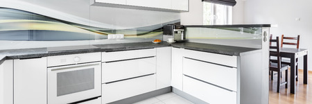 kitchen countertops: Modern kitchen with white furniture and dark countertops and dining table in background, panorama Stock Photo