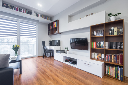 Light and spacious living room with window, TV, bookshelfs, floor panels and modern furniture Banque d'images
