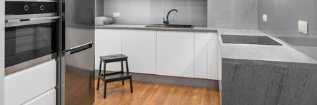Panorama of modern, spacious kitchen with white furniture, wooden floor, silver details and dark step stool