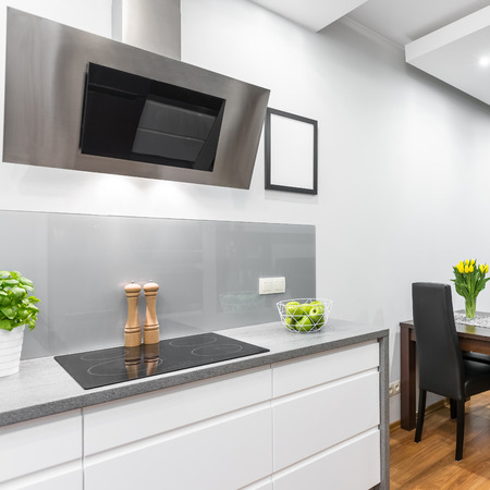White Kitchen With Induction Hob And Exhaust Hood, Open To A Dining Area  Photo