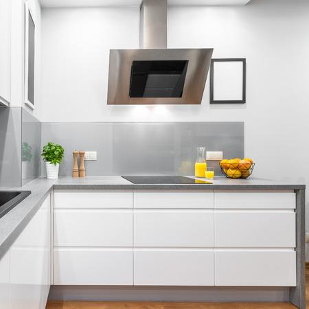 Cocina con muebles blancos modernos, encimera de granito y campana de  extracción