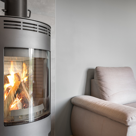 fireplace home: Close up of modern fireplace and comfortable armchair at home Stock Photo