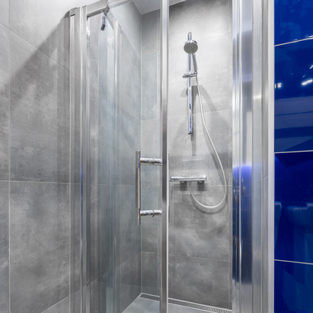 walk in: Modern bathroom with functional walk in shower and tiling in blue and grey