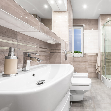 bidet: Spacious high gloss bathroom in beige with basin, mirror, toilet, bidet and shower