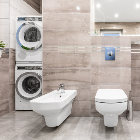 bidet: High gloss bathroom with toilet, bidet, washer and clothes dryer Stock Photo