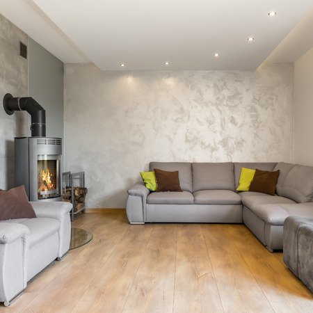 extra large: Living room in grey with extra large sofa and fireplace in industrial style