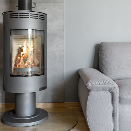fireplace home: Grey home interior with fireplace in industrial style and armchair Stock Photo