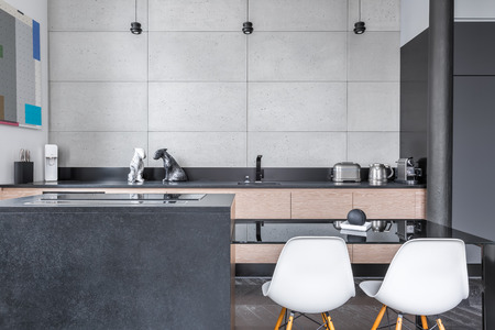 Modern kitchen with black table, white chairs, and grey tiling
