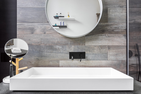 Bathroom with countertop washbasin, mirror and grey tiles