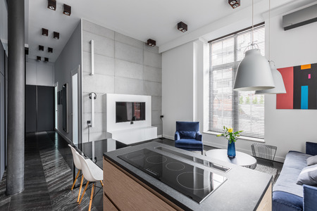 Nice designed flat with grey wall tiles, worktop, television, and window blinds Stock fotó