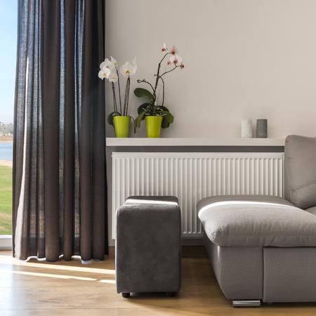 #69584837   Helles Wohnzimmer Mit Bequemen Sofa , Puff  Und Balkontüren Mit  Dekorativem Vorhang, Orchideen, Die Auf Einem Wandregal Stehen