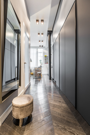 Home corridor with mirror, stool and black sliding wardrobe