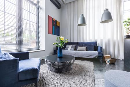 Woonkamer met blauw gestoffeerde meubels, zonwering en witte vitrage Stockfoto