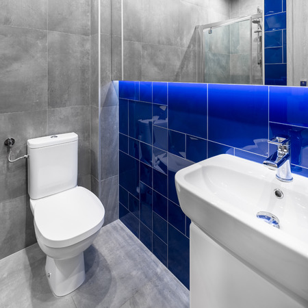 toilet sink: Small bathroom in grey and blue with toilet, sink and basin cabinet