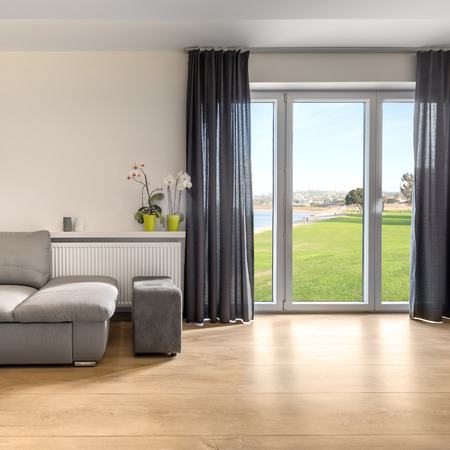 Bright and spacious villa with sofa, wooden floor panels and balcony window with amazing view