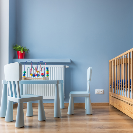 Blue room with childs table, chairs and wooden cot