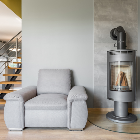 fireplace home: New design home interior with fireplace, comfortable armchair and stairs Stock Photo