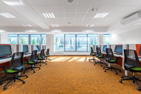 Spaziosa sala informatica con pavimento arancione e parete